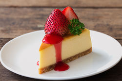 stock-photo-new-york-style-cheesecake-on-white-plate-decorated-with-fresh-strawberry-parsley-and-strawberry-657935272.jpg
